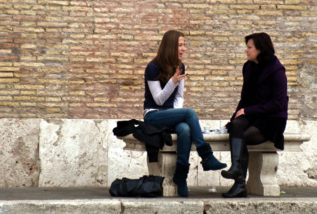 Two women conversing on a bench.