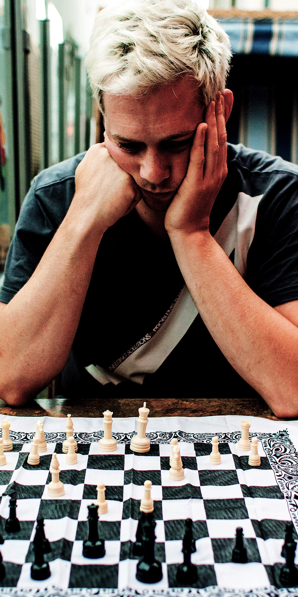 Man contemplating a chess board.